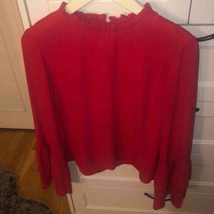 Röd blus med volangärmar, veckad i halsen, stängs med knapp i nacken.