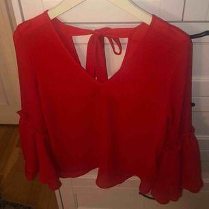 Röd blus med volangärm, djup på fram och baksida, samt en rosett på ryggen