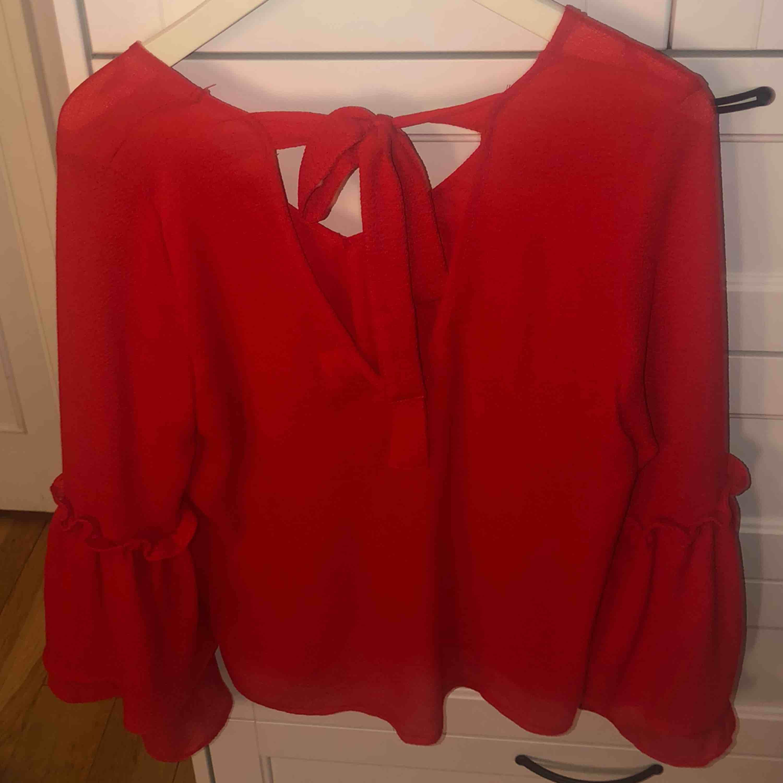 Köparen står för frakt (20kr) annars finns jag i Eskilstuna  Röd blus med volangärm, djup på fram och baksida, samt en rosett på ryggen. Blusar.