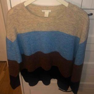 Stickad tröja, randig i beige, ljusblå, brun och mörkblå. Lite större i storleken.