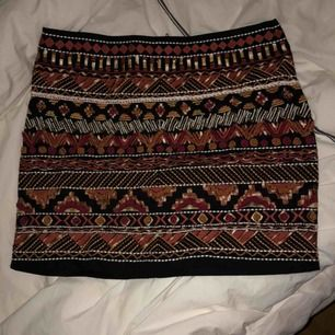 Kort kjol med broderier och pärlor på framsidan
