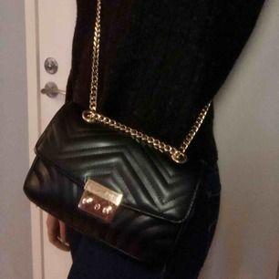 Snygg väska från Nelly i nyskick med guldiga detaljer! Mkt sparsamt använd. Väldigt rymlig trotts att den är rätt så liten (Iphone för skala). Hela väskan är ca 20 cm i bredd och 13 cm i höjd och är gjord i fejkläder. Köparen står för eventuell frakt 🥰