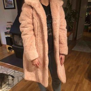 Rosa fuskpäls kappa, i helt okej skick. Stängs med knappar. Längd: 95cm Axelmått: 43cm Kan frakta eller mötas i Eskilstuna, Flen eller Katrineholm🌲
