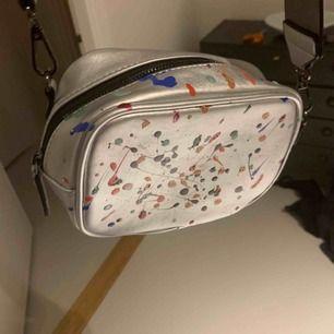 Ascool och unik väska! Passar i alla tillfällen! Den är silvrig och det nedkommer ett silvrigt brett band, men går självklart att använda med ett kortare band/kedja som en baguette bag. Har målat på den själv. Köptes för 300kr