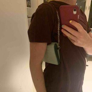Jättefin väska från Carin Wester som funkar till allt! Ganska liten, men rymlig. Det breda gröna bandet ingår, men går att byta band till ett kortare band/kedja om man hellre vill det. Det gröna bandet är även fint till många andra väskor