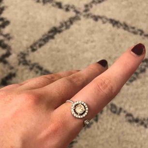Säljer min jätte fina Lily and Rose ring! Det är en ljus rosa sten i mitten och så är det silver stenar runt om. Använd få tal gånger och det är i väldigt bra skick. Köparen står för frakten! 💗