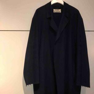 Underbar kappa i ull från Acne Studios - modell Ember Wool. Mörkt marinblå med sömlösa kanter. Tunt bälte i midjan i samma material. I använt men mycket fint skick! Strl 36 som passar 34-38. Ordpris 4000kr. Köpare står för frakt.