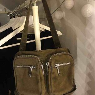 Noella väska köpt här på plick! Säljs pga att den inte kommer till användning. Väskan har lite slitningar (se sista bilden), mellan sizen och militärgrön, långa bandet följer inte med!