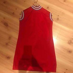 Söt klänning i 60-tals anda! Polyester, klarröd med randiga detaljer. Ingen storlekslapp men gissar på en s-m!