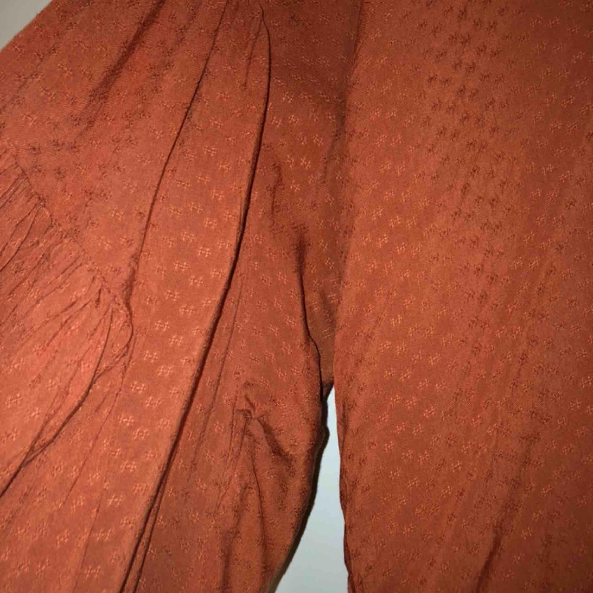 """En fin blus/tunika med vida ärmar. Resår längs ut i armarna som går att dra upp som jag gjort på bild 1,2. Snören att knyta vid halsen. """"Prickigt"""" tunt material. Passar Stl L/M. aldrig använd. Blusar."""