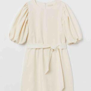 Superfin slutsåld klänning från HM trend. Gräddvit med puffärmar och bälte. Storlek s.