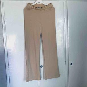 Beiga byxor med vida ben. Gjorde av 95% polyester och 5% elastan. Från NLY trend i strl M, aldrig använda.