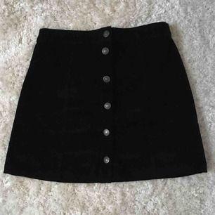 Svart manchesterkjol med knappar från Bershka. Bekväm längd och är i bra skick.  Kan mötas upp eller frakta, frakt tillkommer! 🧡