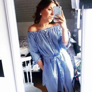 Vit-blå-randig klänning från Boston! Passar både XS och M, du väljer själv hur hårt du vill dra åt skärpet
