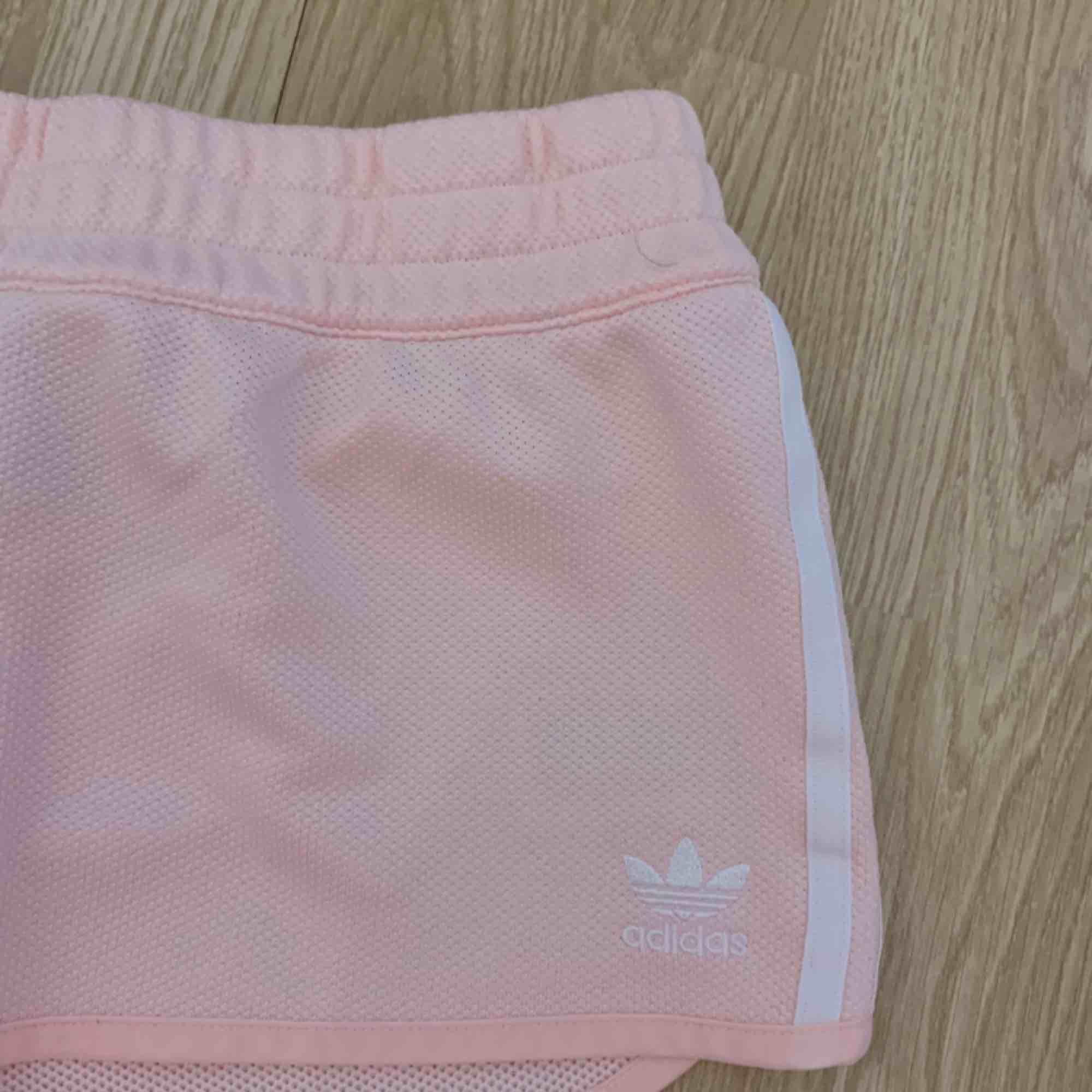 Rosa adidas shorts storlek 38, fint skick.  Möts upp i Stockholm eller fraktar.  Frakt kostar 54kr extra, postar med videobevis/bildbevis. Jag garanterar en snabb pålitlig affär!✨. Shorts.