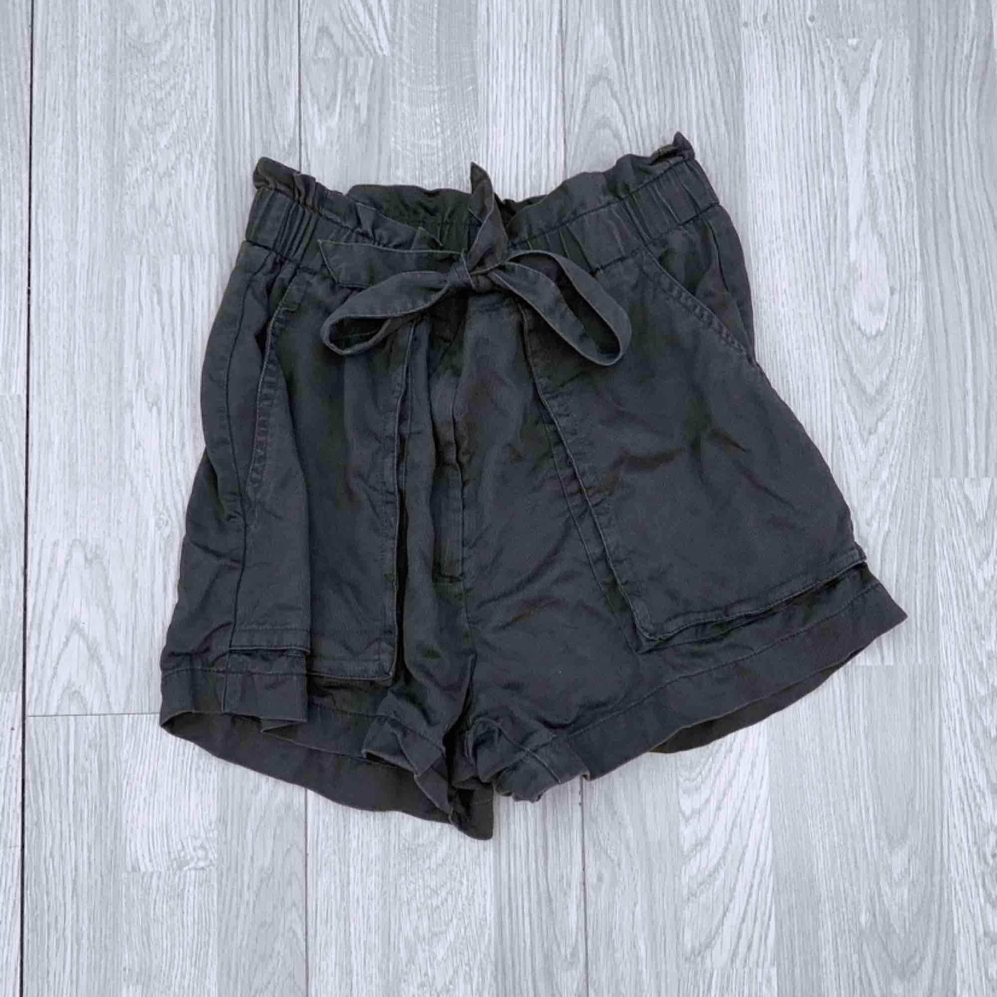 Grå/gröna högmidjade shorts man knyter, storlek 44 från hm.  Passar mindre om man vill ha dem oversized. Använt skick.  Möts upp i Stockholm eller fraktar.  Frakt kostar 59kr extra, postar med videobevis/bildbevis. Jag garanterar en snabb pålitlig affär!✨. Shorts.