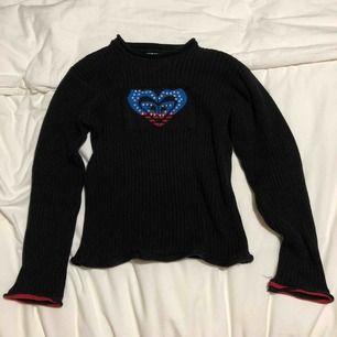 Svart tröja med ett USA hjärta i mitten. Fått av en kompis och sen har jag använt det flera gånger så den är väl använd och det märks. Sydd på vänstra axeln och trådar löser upp runt hjärtat.