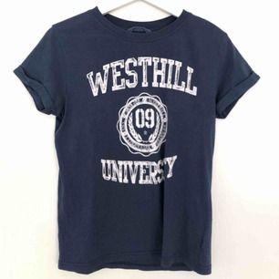 Blå t-shirt med vitt tryck, aldrig använd. Frakt ingår inte i priset:)