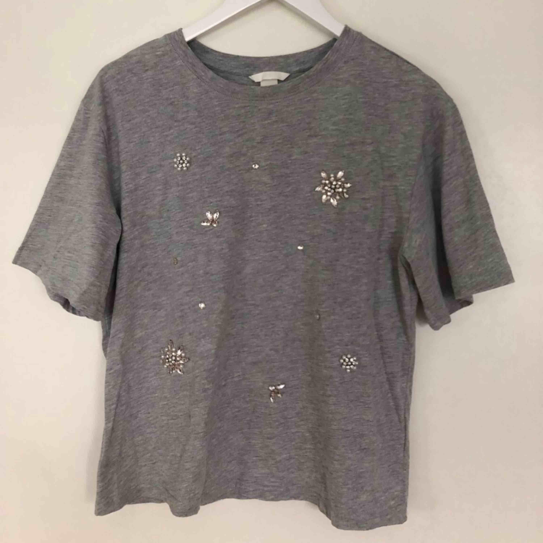 Grå t-shirt med stenar/diamanter på, aldrig använd. Frakt ingår inte i priset:). T-shirts.