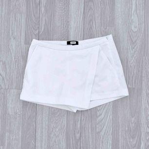 """Vit kort """"skort"""" (kjol/shorts) från Bikbok storlek XS i fint skick.  Möts upp i Stockholm eller fraktar.  Frakt kostar 36kr extra, postar med videobevis/bildbevis. Jag garanterar en snabb pålitlig affär!✨"""