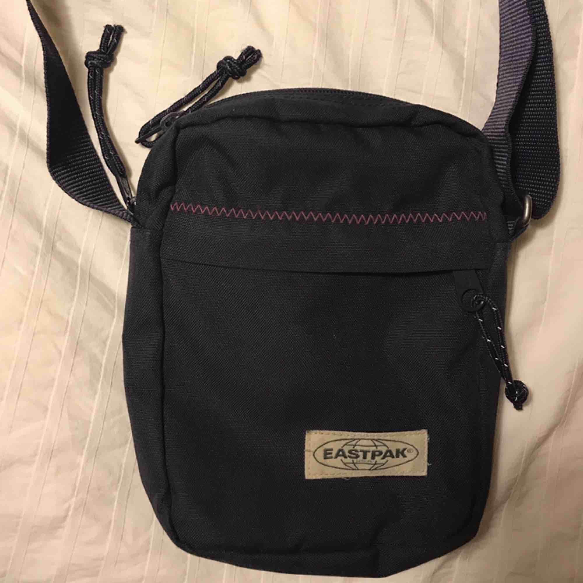 asfin mörkblå eastpak väska med lila sömmar! mkt bra skick! nypris ca 300kr. Fraktar eller möts vid slussen!. Väskor.