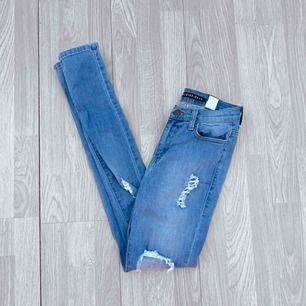 Högmidjade blå ripped jeans från Fashion nova storlek 1 (XS) fint skick.  Möts upp i Stockholm eller fraktar.  Frakt kostar 63kr extra, postar med videobevis/bildbevis. Jag garanterar en snabb pålitlig affär!✨