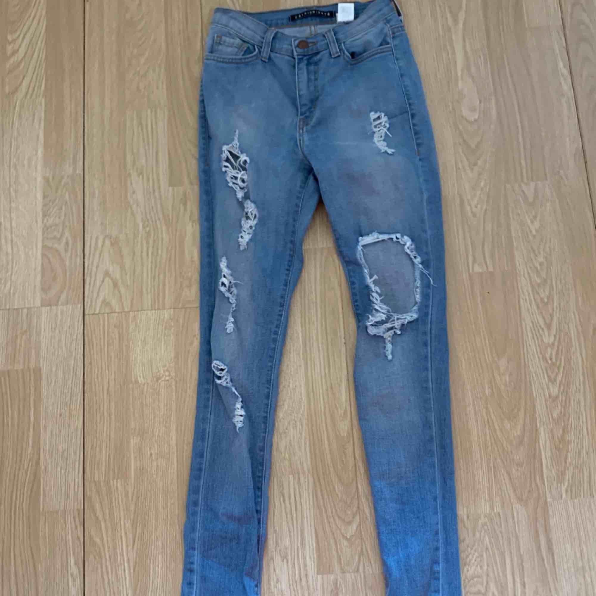 Högmidjade blå ripped jeans från Fashion nova storlek 1 (XS) fint skick.  Möts upp i Stockholm eller fraktar.  Frakt kostar 63kr extra, postar med videobevis/bildbevis. Jag garanterar en snabb pålitlig affär!✨. Jeans & Byxor.