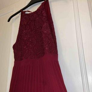 Balklänning i vinröd färg. Spets på överdelen, dragkedja och knyte där bak vilket gör att man kan man kan vara större än XS då man kan välja hur man vill ha den. Den är uppsydd till mig som är 165cm lång (med klackar)