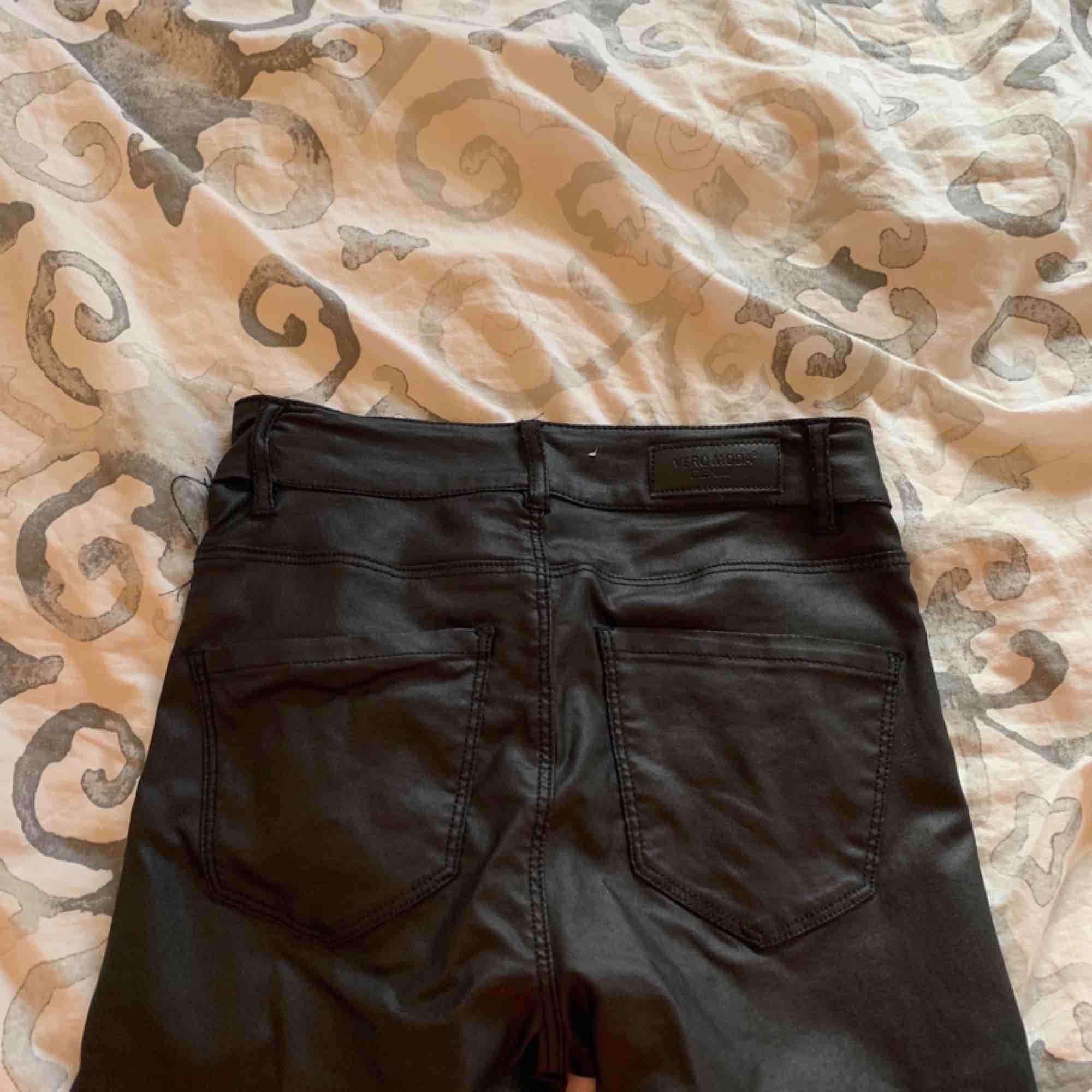 Högmidjade svarta jeans i fake skinn från vero moda storlek xs, fint skick förutom ett hål, går att laga. Möts upp i Stockholm eller fraktar.  Frakt kostar 59kr extra, postar med videobevis/bildbevis. Jag garanterar en snabb pålitlig affär!✨. Jeans & Byxor.