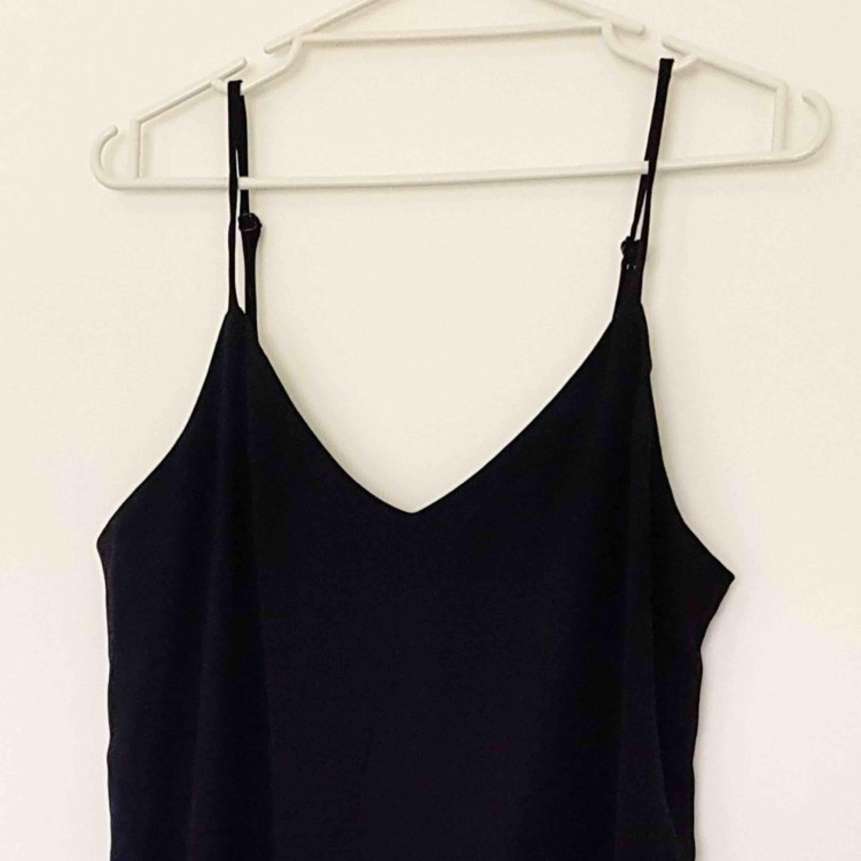 Svart stilren långklänning från Monki. Justerbara band och v-ringad urringning. Snygg över tex en t-shirt! . Klänningar.