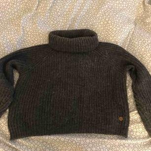 En mörkgrå stickad polotröja ifrån Kappahls egna märke tror jag. Sticks inte. Köparen står för frakten