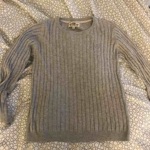 En kabelstickad grå tröja ifrån Hampton republic ifrån kapphal. Är väldigt stretchig. Köparen står för frakten