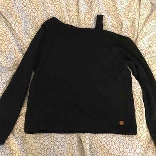 En svart tröja som har ena axeln lite offshoulder men men ett band som håller upp typ. Aldrig använd. Köparen står för frakten