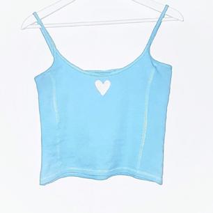Supersött babyblått linne med ett vitt broderat hjärta. Frakt tillkommer på 18 kr ❤