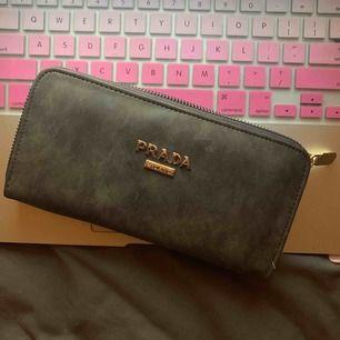 Prada plånbok i mocka-material (oäkta) men i riktigt bra kvalité! Aldrig använd   Möts upp i Stockholm, annars står köparen för frakt:)