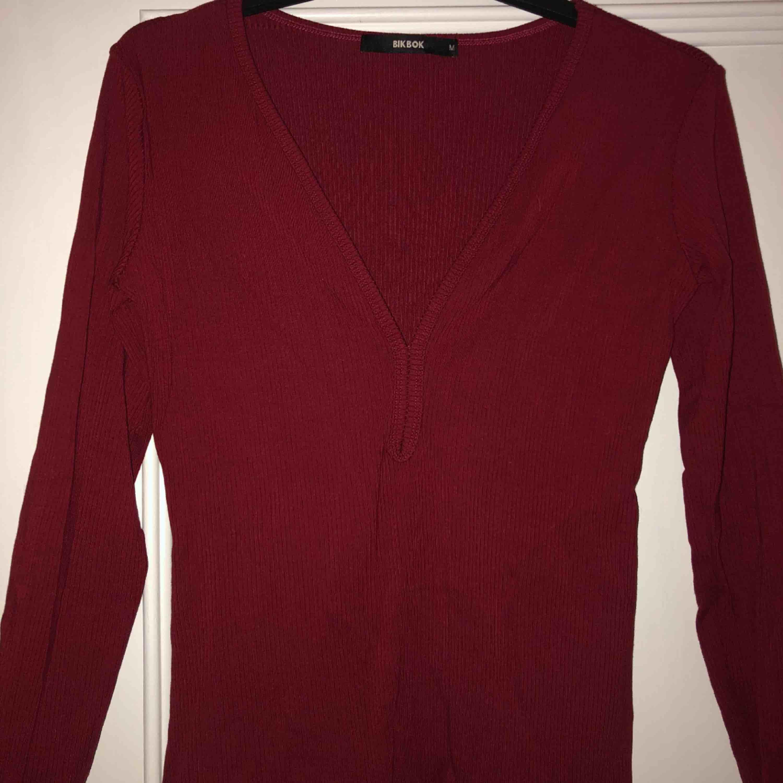 En fin ribbad, vinröd tröja, med djup urringning och ett fint skick🕊🕊. Toppar.