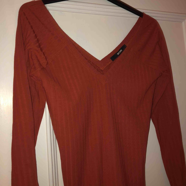 En fin och användbar tröja med djup V-ringad både fram och bak och i en röd/orange färg🧡❤️ endast använd två gånger. Toppar.