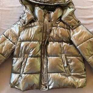 En silvrig dunjacka, perfekt till vintern då den är varm. Använd väldigt försiktigt, inga skador, condition 9/10