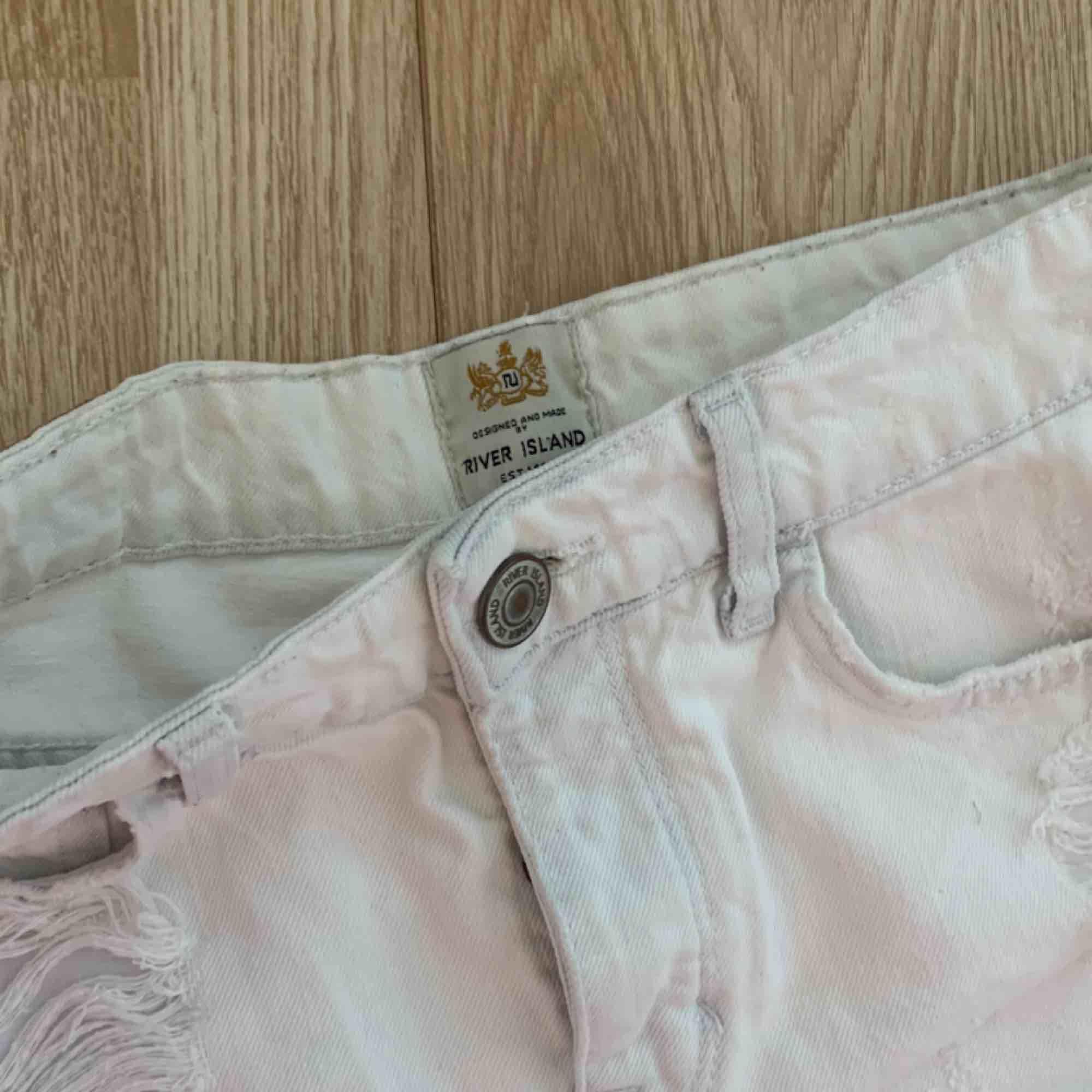 Supersnygga vita högmidjade korta ripped shorts från River Island, bra skick förutom småfläckar. Storlek 8 (36/S)  Möts upp i Stockholm eller fraktar. Frakt kostar 55kr extra, postar med videobevis/bildbevis. Jag garanterar en snabb pålitlig affär!✨. Shorts.