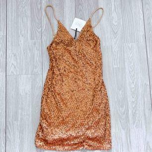 NY copparfärgad klänning från Nelly storlek XS, prislapp kvar.  Möts upp i Stockholm eller fraktar. Frakt kostar 42kr extra, postar med videobevis/bildbevis. Jag garanterar en snabb pålitlig affär!✨