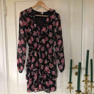 """Super söt klänning med rosa blommor på💗💗 Den är i ett liknade """"mesh"""" material💗 är v-ringad vid bröstet och har volanger som detaljer💗💗"""