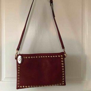 Härlig röd väska med guldiga detaljer❤️❤️ har två olika band så man kan bära den lite olika❤️ har olika fack inuti och är stängbar❤️ aldrig använd!