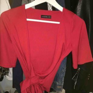 En röd tröja från even&odd. Ni ser på bild 3 hur tröjan sitter på!Använd en gång och är fortfarande i nyskick. Skulle säga att tröjan passar både S/M