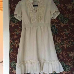 Crémefärgad klänning med krås och v-neck. Liten volang vid kjolslutet. Några noppror på men kan ta bort dom om jag hinner köpa batterier till min noppmaskin innan sälj. Köparen står för frakt 💌