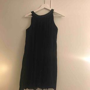 En svart plisserad klänning ifrån ellos. Använd 2 ggr. Har paljetter runt halsen. Köparen står för frakten