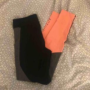 """Ett par träningstajts ifrån hm sport. Är svarta, grå och lite neon orange typ. På ena benet står det """"ACTIVE SQUAD"""". Köparen står för frakten"""