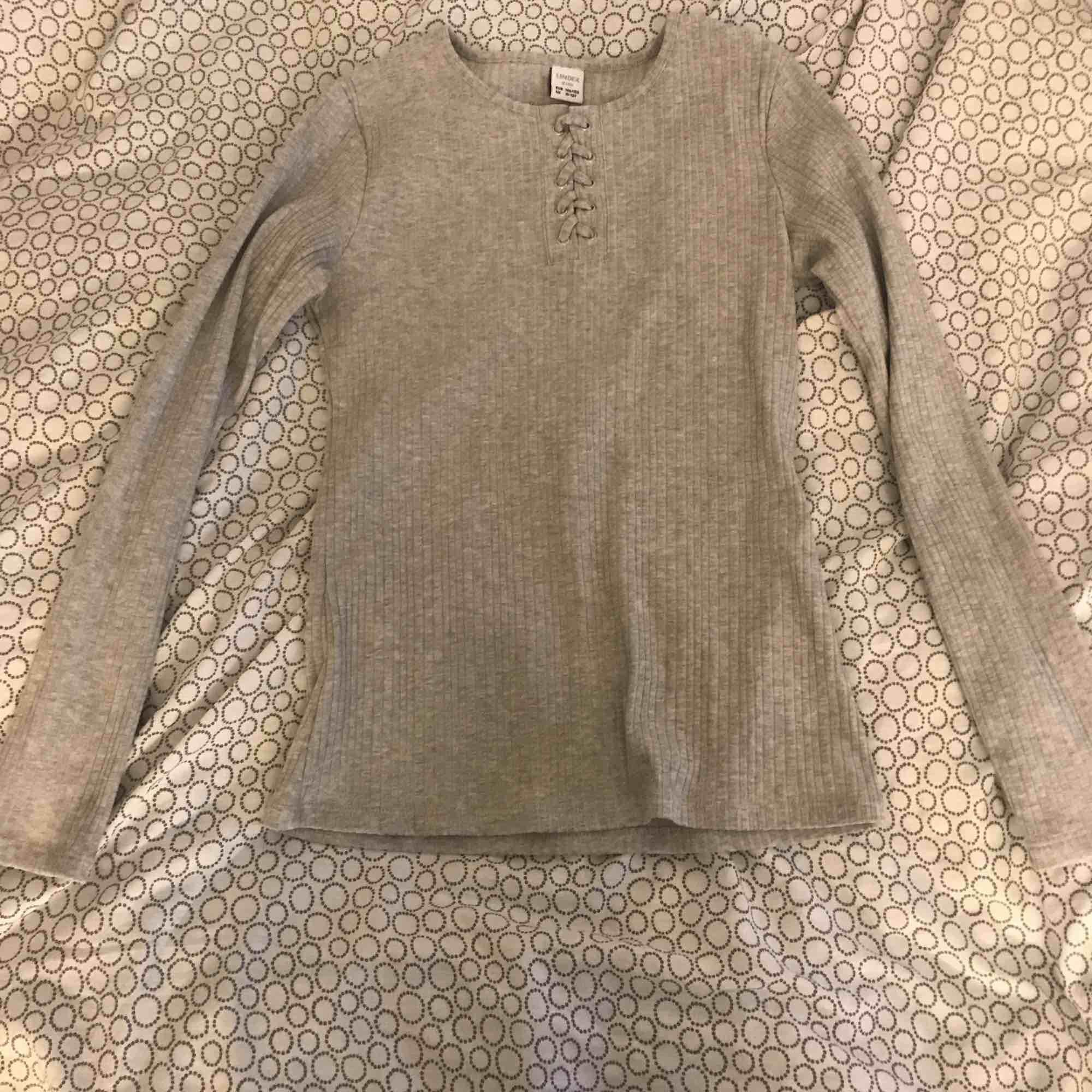 En ljusgrå ribbad tröja ifrån Lindex. Den har lite snörning på framsidan. Använd 2 gånger. Köparen står för frakten . Toppar.