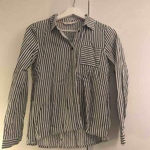 En svart och vit randig skjorta ifrån hm. Har en ficka på bröstet. Köparen står för frakten