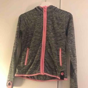 En grå och neon rosa tränings kofta. Har en liten tråd som sticker ut ur fickan men går säkert att klippa av. Köparen står för frakten