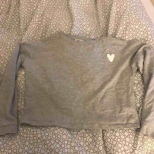 En ljusgrå cropad sweatshirt ifrån hm. Den har ett litet vit hjärta. Köparen står för frakten